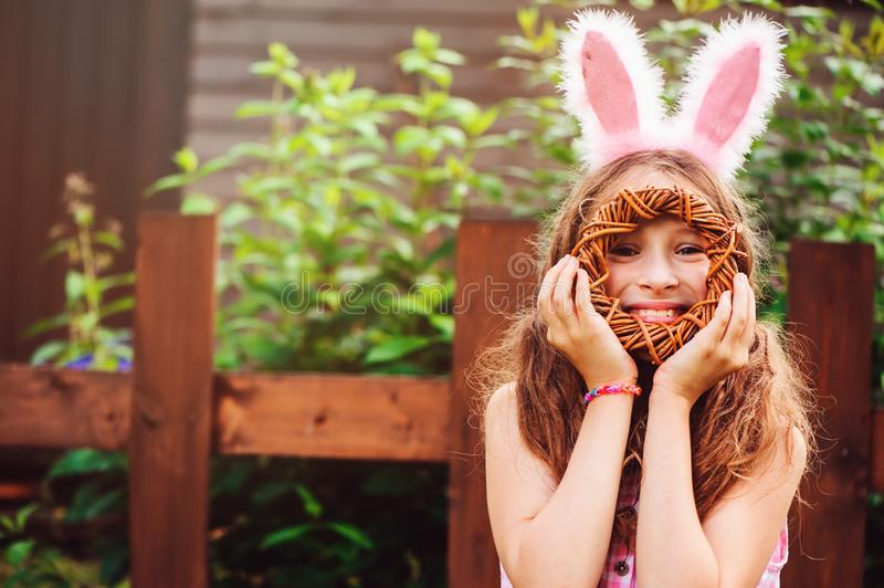 Easter portrait of happy child girl in funny bunny ears playing egg hunt outdoor stock image