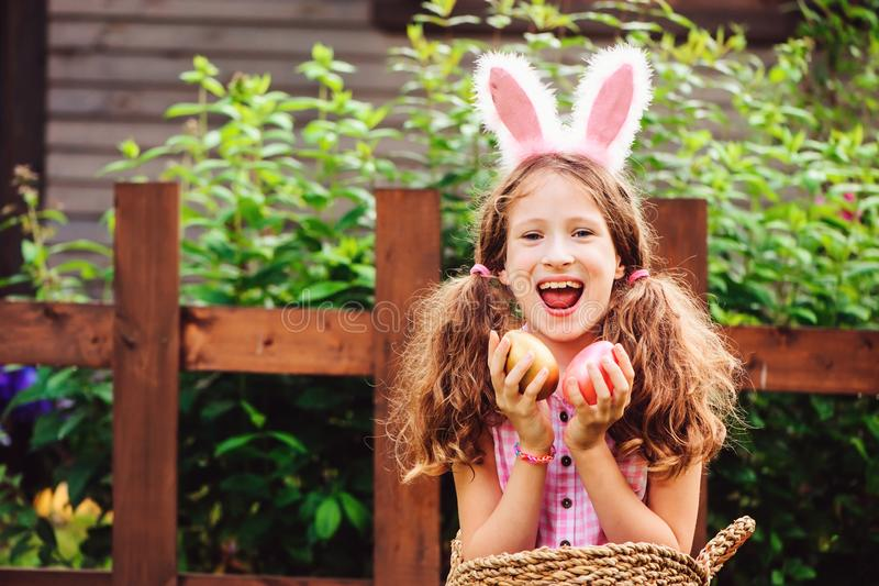 Easter portrait of happy child girl in funny bunny ears playing egg hunt outdoor. At wooden country house royalty free stock photography