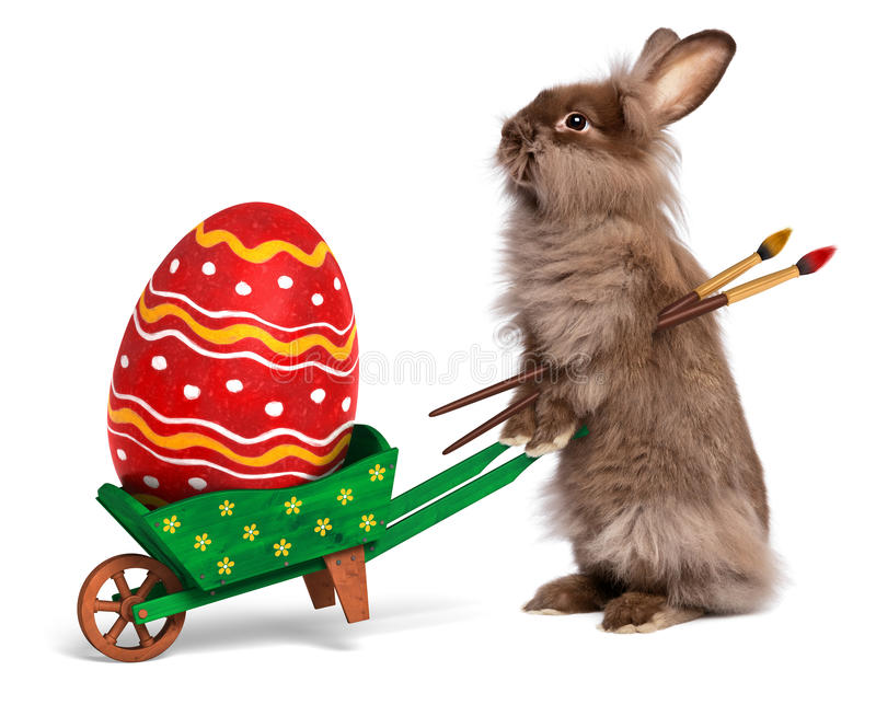 Funny Easter rabbit with a wheelbarrow and an East. Cute Easter bunny rabbit with a little green wheelbarrow and a red painted Easter egg, isolated on white, CG