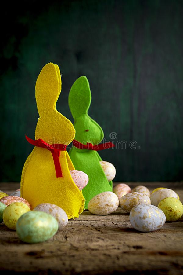 Easter rabbits with eggs on wooden table. stock image
