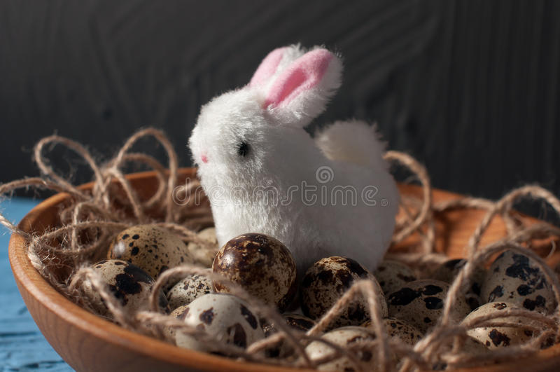 Easter rabbits and quail eggs in wooden bowl on background close up stock photos