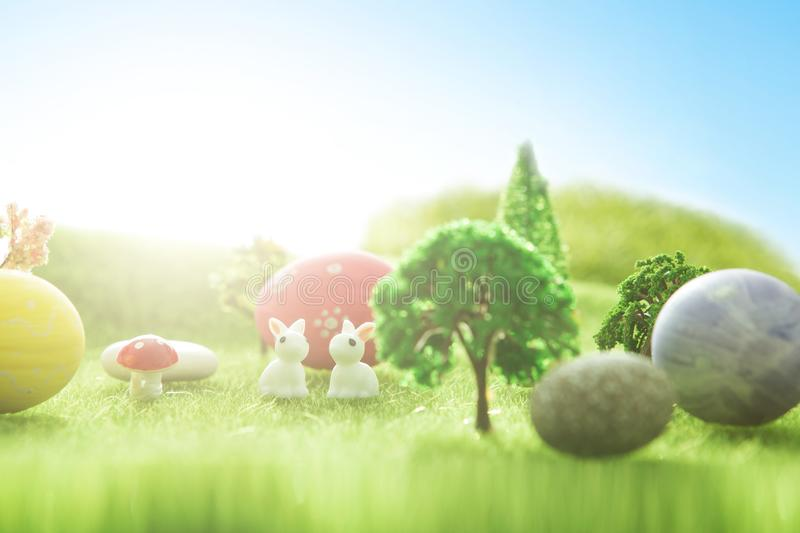 Easter rabbits toys with easter eggs on green grass. Fairy tale sunset on the green field with grass, mushrooms and trees. Macro. Easter rabbits toys with easter stock photography