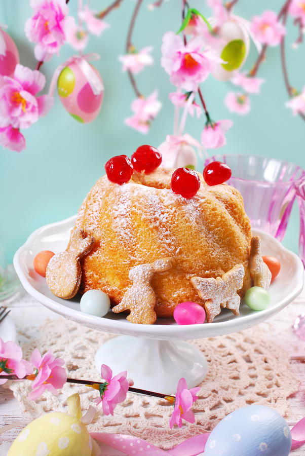 Easter ring cake with cherry decoration and icing sugar. Easter ring cake with maraschino cherry decoration and icing sugar on pastel color floral background royalty free stock images