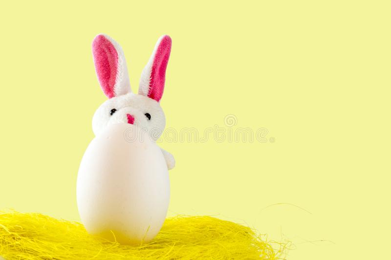 White egg, easter bunny,, yellow background. Easter scene with colored eggs, easter bunny,, yellow background royalty free stock photos