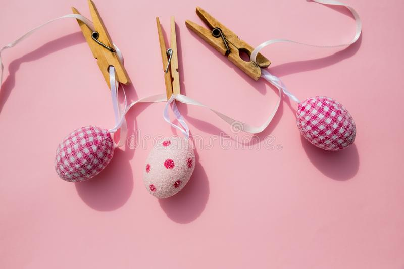 Easter scene with row of hanging colored eggs and pin isolated on pink background. Happy easter composition for spring stock photo