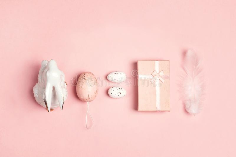 Easter set of decorative bunny, eggs, feather and gift box pink background stock images