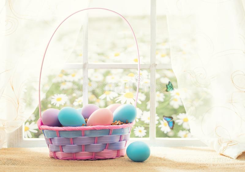 Easter shopping theme: colorful eggs in a basket on the window in a sunny day with butterflies. Easter shopping theme: colorful eggs in a basket on the window in royalty free stock photography