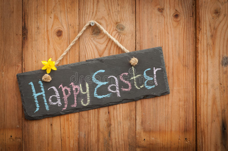 Easter Sign. Happy Easter in colourful chalk on slate sign with wooden background stock photos
