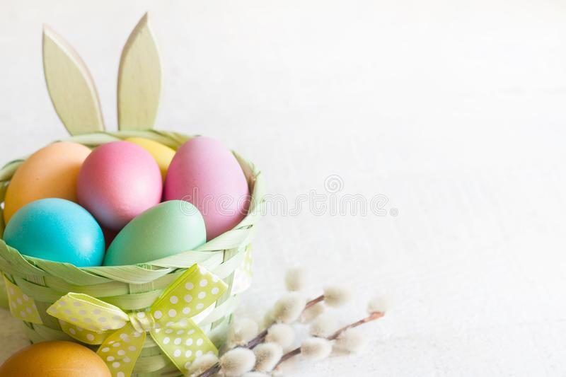 Easter simple colorfgul eggs in the basket and bunny on white wooden background. Closeup stock photos