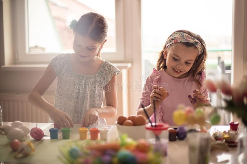 Easter is something special for them. Little girls coloring Easter egg royalty free stock image