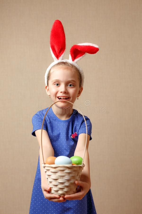 Cute little child wearing bunny ears on Easter day. Girl holding basket with painted eggs. royalty free stock images