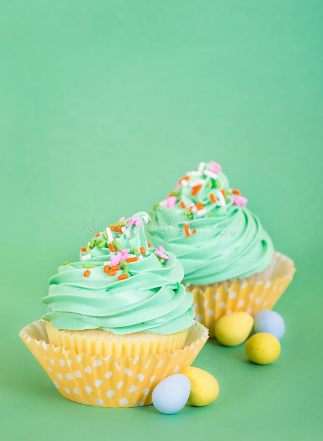 Easter spring cupcakes with candy eggs on green royalty free stock image
