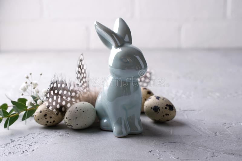 Easter spring decorative composition with easter quail eggs and leaf sprigs of eucalyptus and ceramic bunny. On a gray concrete background with place for text royalty free stock photo