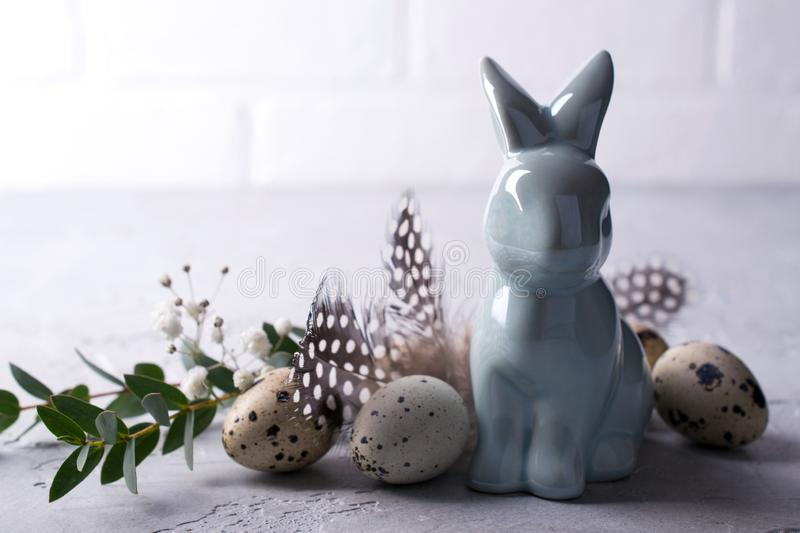 Easter spring decorative composition with easter quail eggs and leaf sprigs of eucalyptus and ceramic bunny. On a gray concrete background with place for text stock images