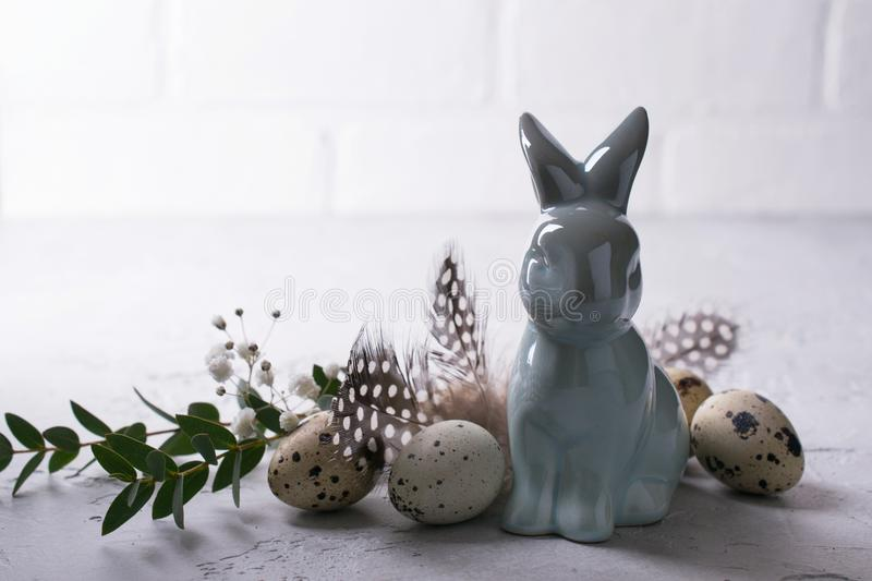 Easter spring decorative composition with easter quail eggs and leaf sprigs of eucalyptus and ceramic bunny. On a gray concrete. Background with place for text stock images