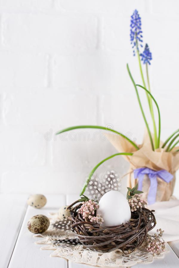 Easter spring decorative composition with white chicken egg in a nest with flowers. Holiday decorations. Easter festive table setting royalty free stock photography