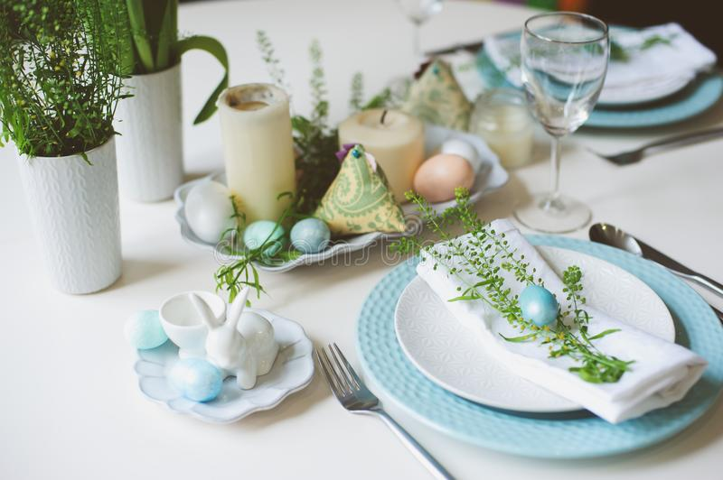 Easter and spring festive table decorated in blue and white tones in natural rustic style, with eggs, bunny, fresh flowers royalty free stock photo