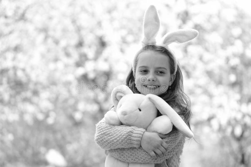 Easter and spring. Happy girl holding pink rabbit in garden with blossoming trees. Childhood, youth and growth. Child stock images