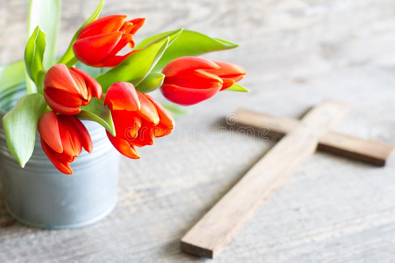 Easter spring red tulips and cross on abstract wooden background royalty free stock photo