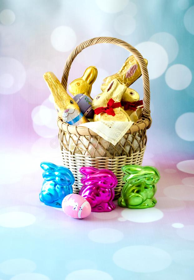 Easter still life with a basket of decorations. An easter basket of chocolate, gold foiled bunnie, and colorful molded rabbits filled with chocolate. Also a few royalty free stock images