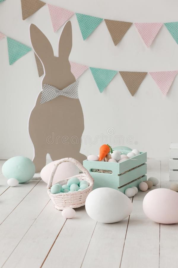 Easter still-life with eggs, carrots bunny paper silhouette and garland on wall. Copy space background stock image