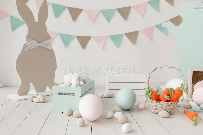 Easter still-life with eggs, carrots bunny paper silhouette and garland on wall. Copy space background royalty free stock photography