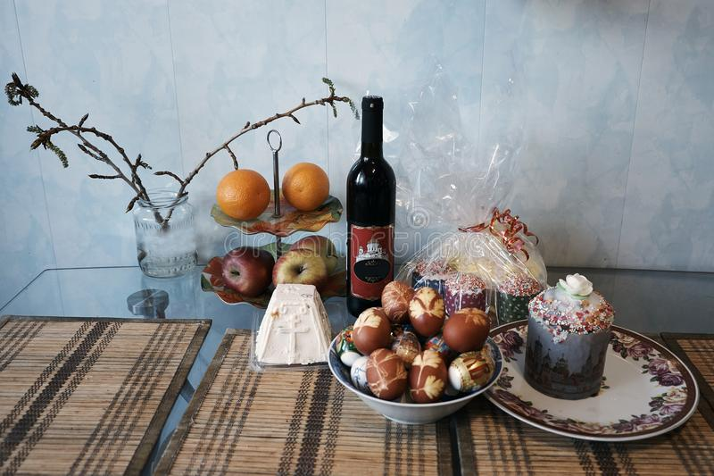 Easter still-life with wine, Easter cakes and the painted egg. Christian holidays photos of Easter food in a rustic style. The table is covered with Easter cakes stock photography