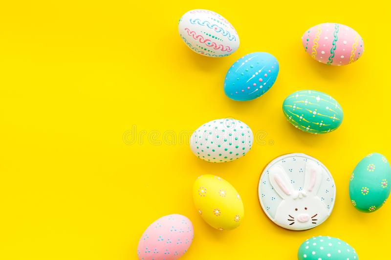 Easter symbols. Colorful Easter eggs and gingerbread on yellow background space for text stock photos