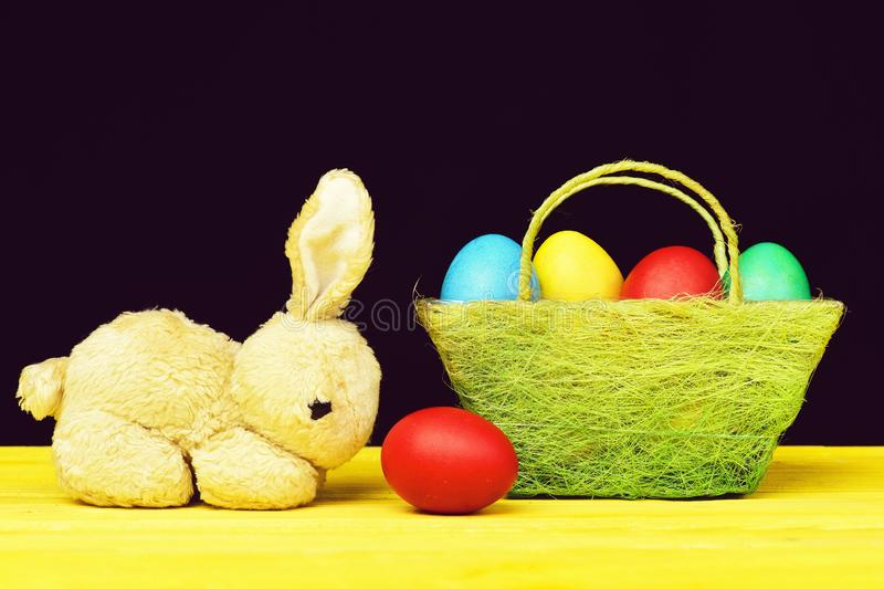 Easter symbols composition. Toy bunny and painted Easter eggs in different colours standing on yellow wooden table stock photography