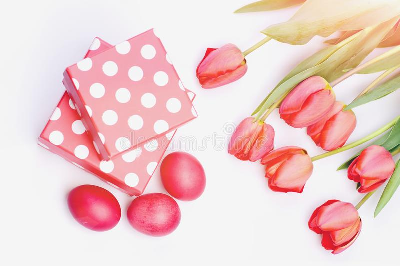 Easter symbols concept. Bunch of flowers near pink present boxes stock photography