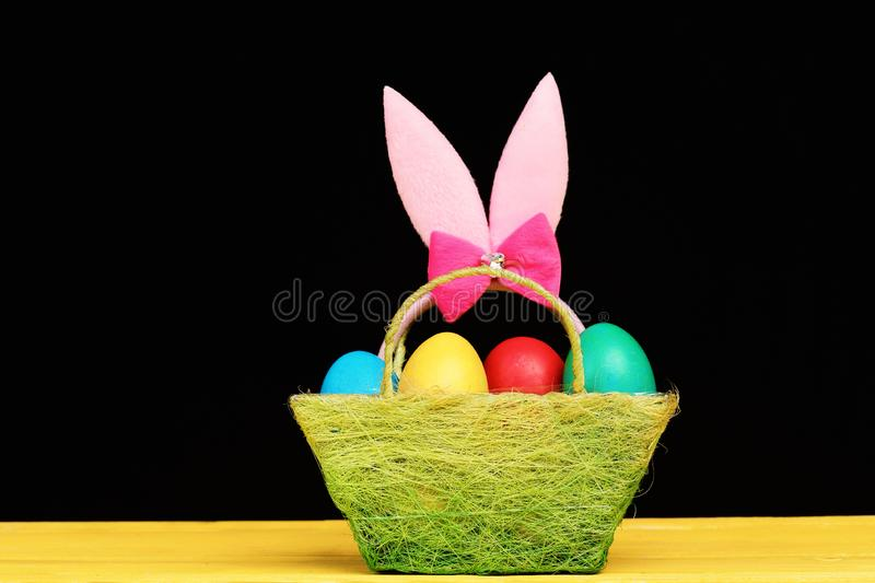 Easter symbols concept. Fluffy rabbit ears with colorful eggs. In green cloth basket. Bunny ears head band in pink color in basket on black background. Easter stock images