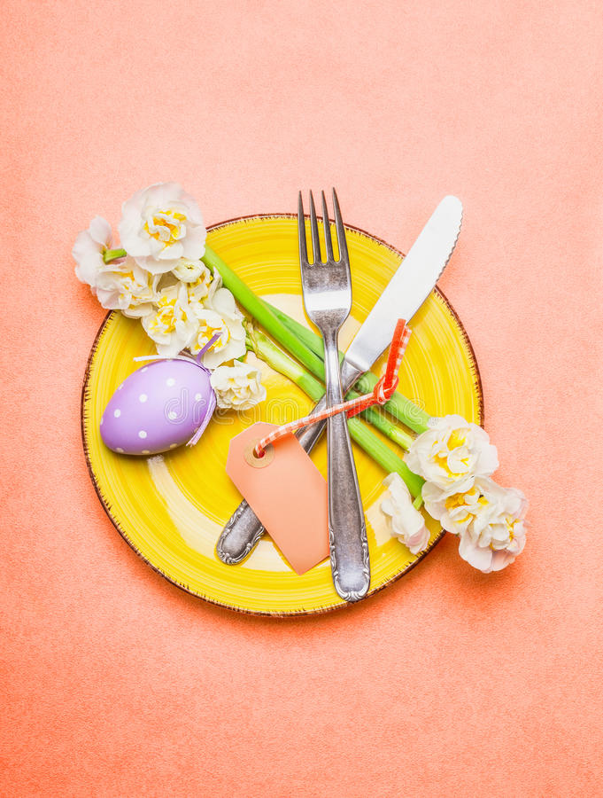 Easter table place setting with daffodils flowers, cutlery, plate, eggs and empty label card on pastel pink background, top view. Place for text stock photography