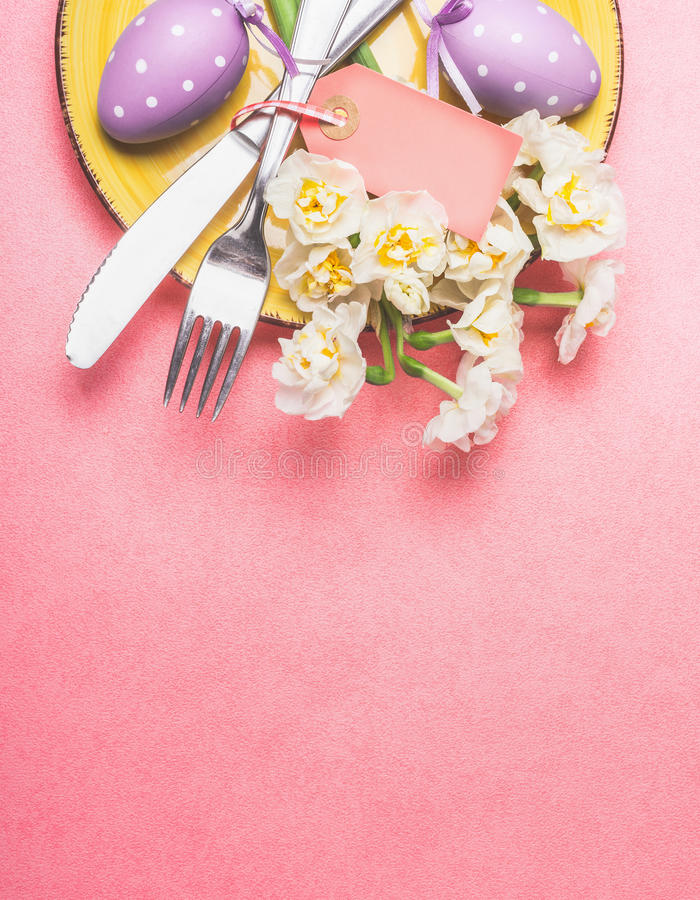 Easter table place setting with nice daffodils , cutlery, plate and eggs on pastel pink background, top view stock image