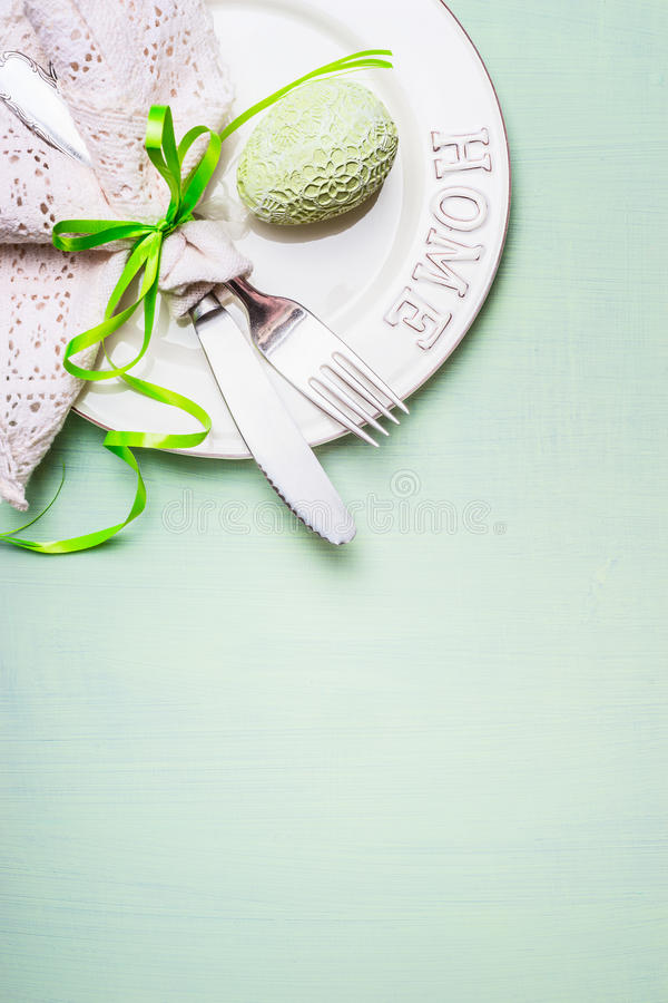 Easter table place setting with plate, cutlery decorated with lacy napkin and egg on light green background, top view. stock image