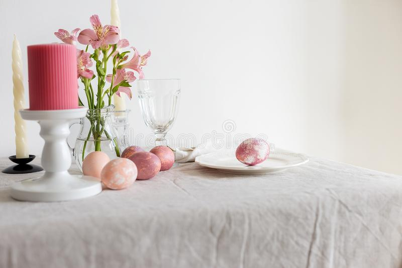 Easter table set on linen tablecloth with Easter egg on plate with decor stock photos