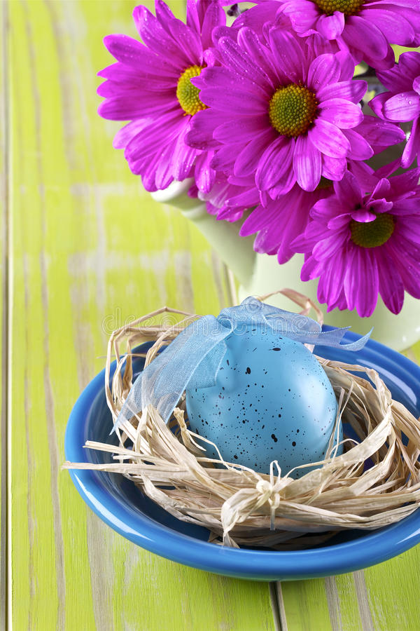 Easter table setting. Daisy and decorative Easter egg,straw and bowl on yellow background royalty free stock image