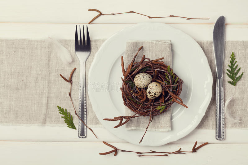 Easter table setting with eggs and spring decoration on rustic background, vintage toning stock photo
