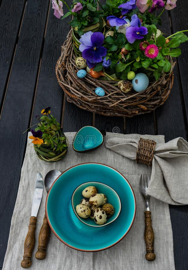 Easter table setting. Festive table setting for Easter holiday dinner decorated with flowers and eggs stock photos