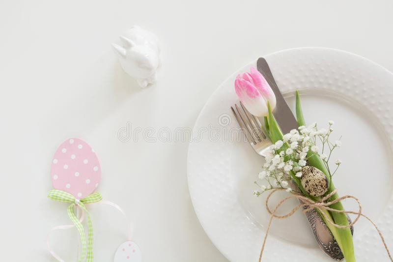 Easter table setting with pink ribbon and tulip on white background. Spring dinner. Top view and copy space for your text. stock photography