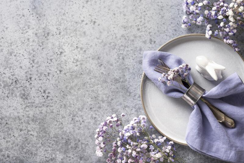 Easter table setting with violet decor on grey stone table. Top view. Space for text. Easter table setting with grey plate and violet decor on grey stone table royalty free stock photography