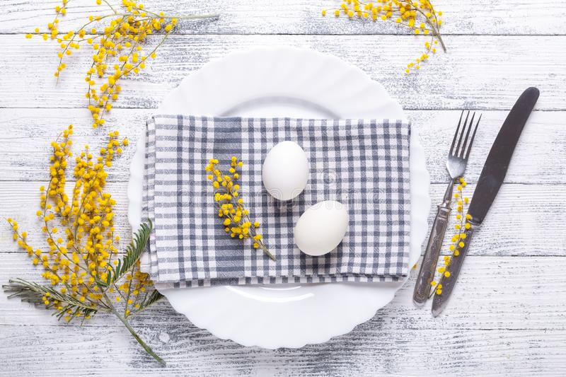Easter table setting. White eggs, napkin on a plate, mimosa flowers, fork, knife on a wooden table royalty free stock image