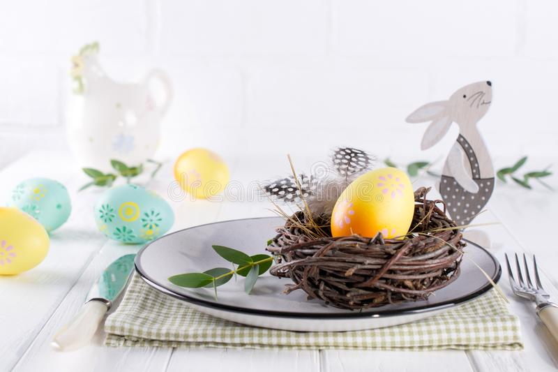 Easter table setting with white plate, textile napkin yellow decorative chicken egg in the nest, mimosa flowers, feathers. And spring easter decoration on white stock images