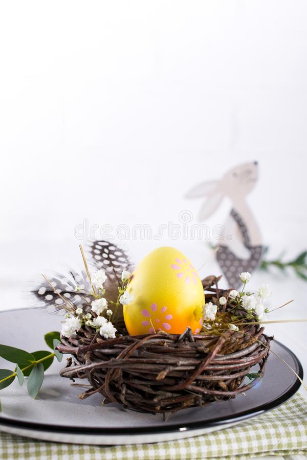Easter table setting with white plate, textile napkin yellow decorative chicken egg in the nest, mimosa flowers, feathers. And spring easter decoration on white royalty free stock image