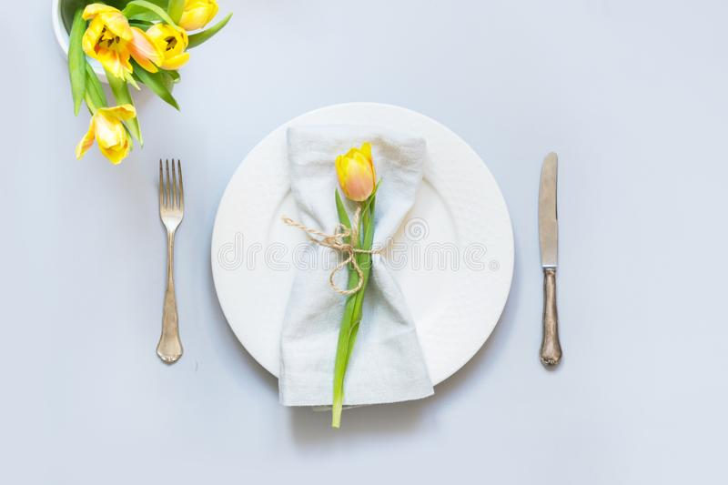 Easter table setting with yellow tulip on pastel blue. Top view royalty free stock photo