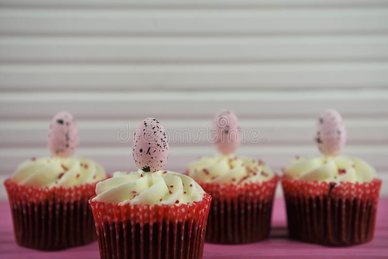 Easter time chocolate flavour cupcakes topped with pink egg decorations on a wood pink table. Easter time with delicious homemade baked chocolate and buttercream royalty free stock photography