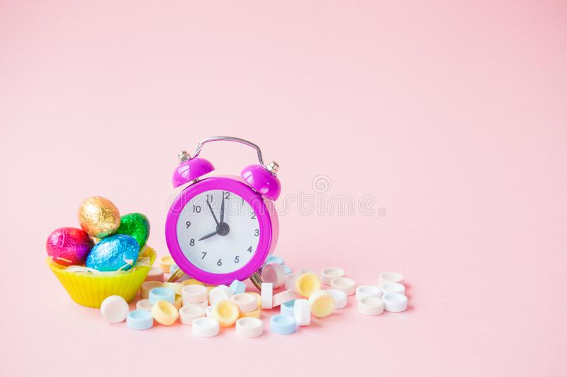Easter Time Concept with alarm clock. On color background royalty free stock image