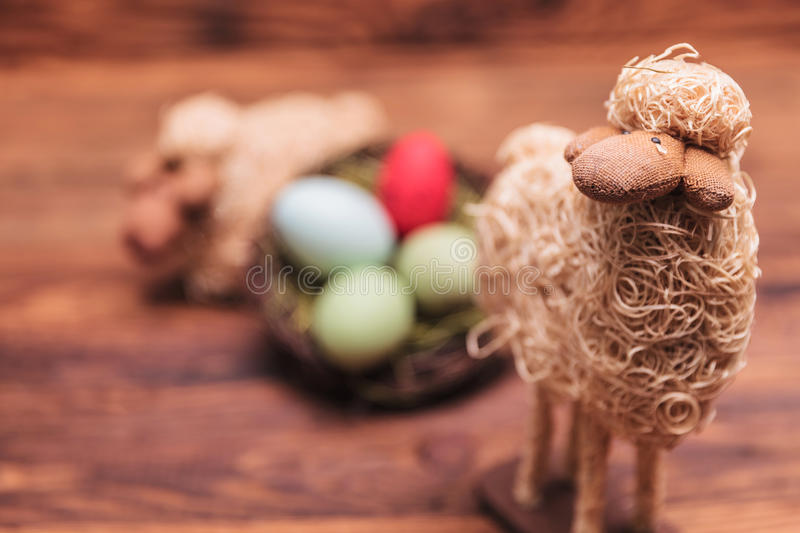 Easter toy sheep in fron of egg basket. On old wood background royalty free stock photos