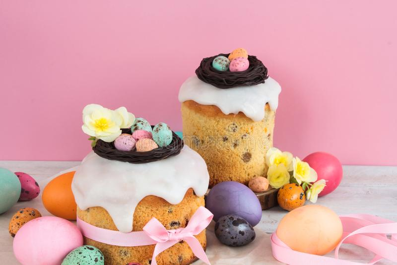 Easter traditional cake with chocolate nest, candy and quail eggs decoration blossom flowers, colorful spring stillife in soft lig. Ht and trendy pastel colors stock photography