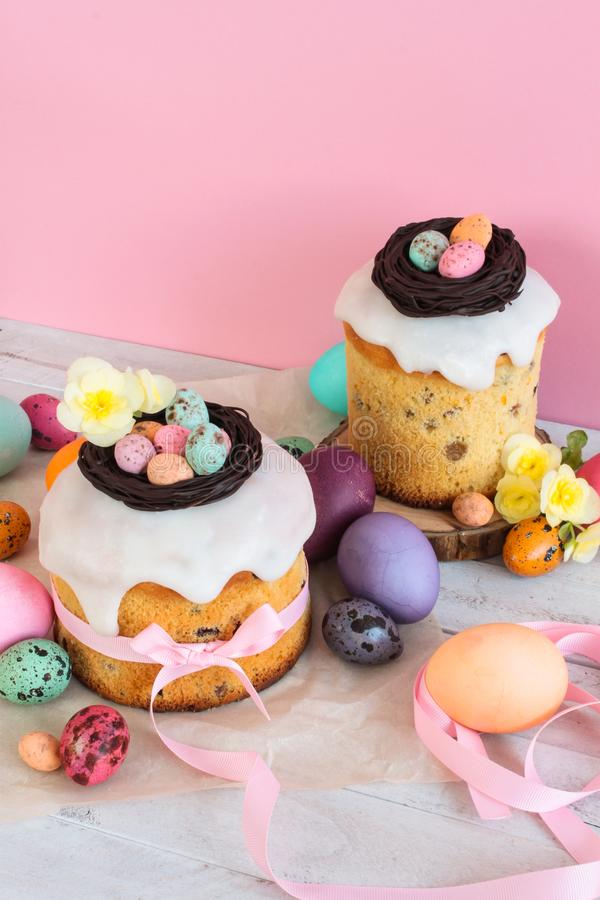 Easter traditional cake with chocolate nest, candy and quail eggs decoration blossom flowers, colorful spring stillife in soft lig. Ht and trendy pastel colors royalty free stock image