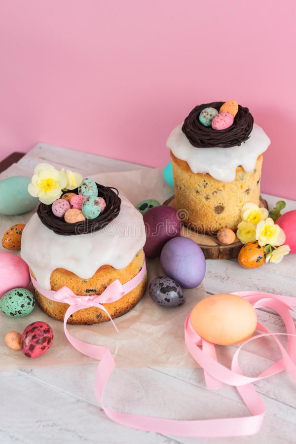 Easter traditional cake with chocolate nest, candy and quail eggs decoration blossom flowers, colorful spring stillife in soft lig. Ht and trendy pastel colors stock photo